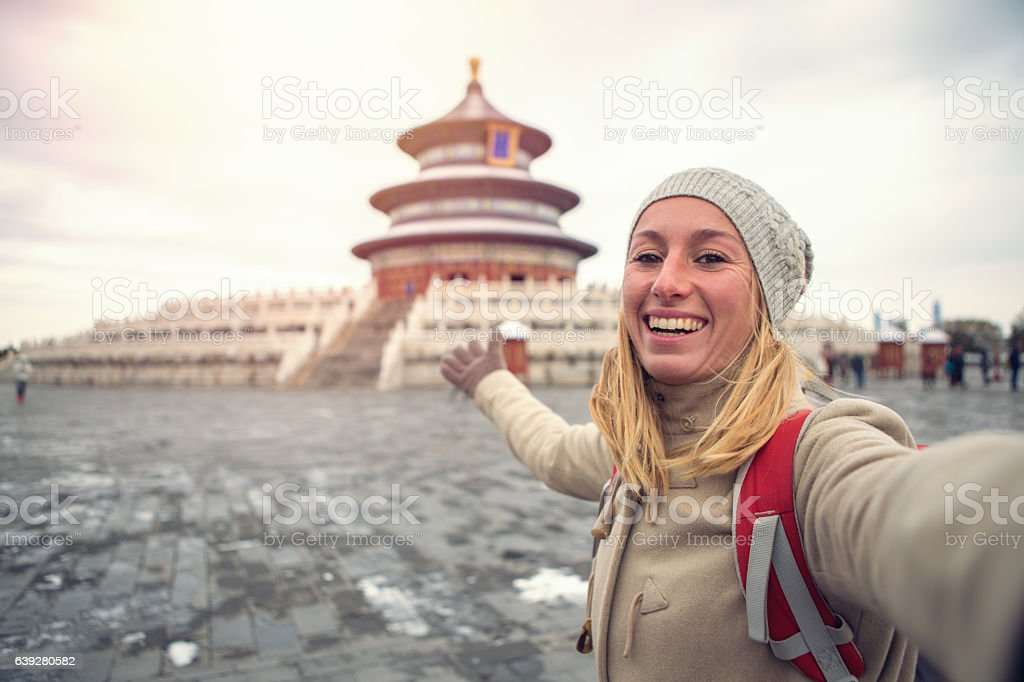Young woman traveling takes selfie with Temple of Heaven,Beijing stock photo