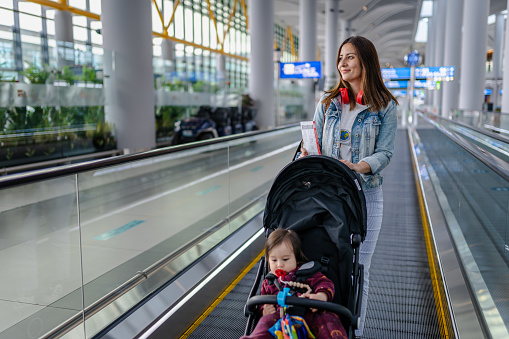 Young Woman traveling with her baby for the first time after the COVID-19