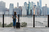 Young woman travelling in New York with suitcase