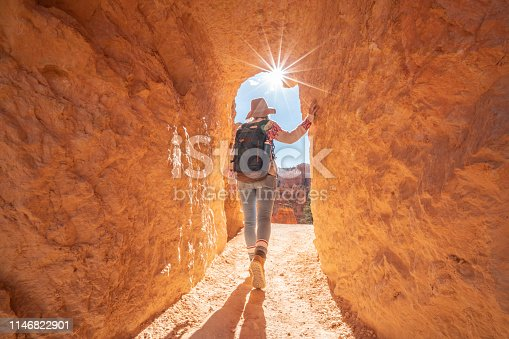 Young woman travels Bryce Canyon national park in Utah, United States, people travel explore nature. Girl hiking in red rock formations
