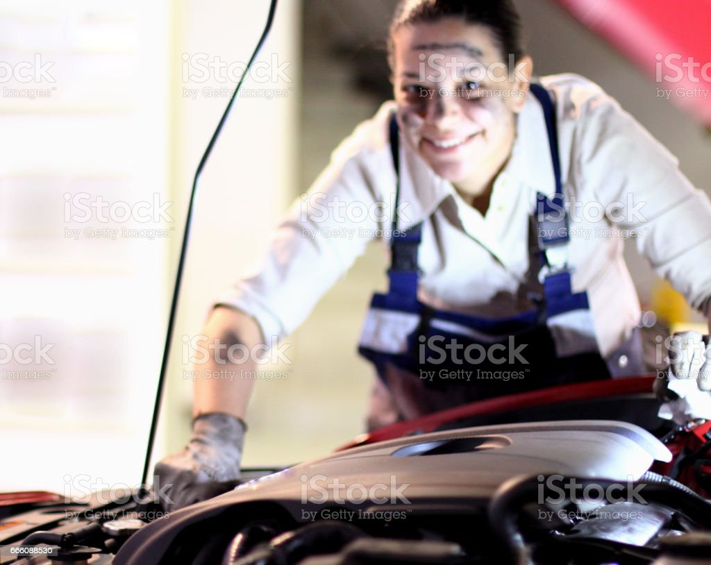 Young woman tries to fix broken car stock photo