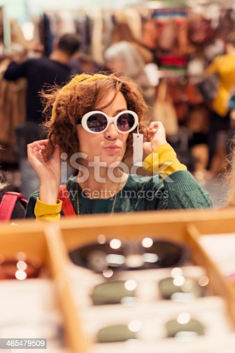 Young woman trying glasses in vintage thrift market. Blurred people in background.