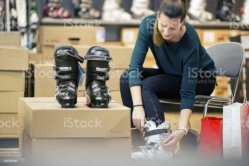 A young woman trying on ski boots stock photo