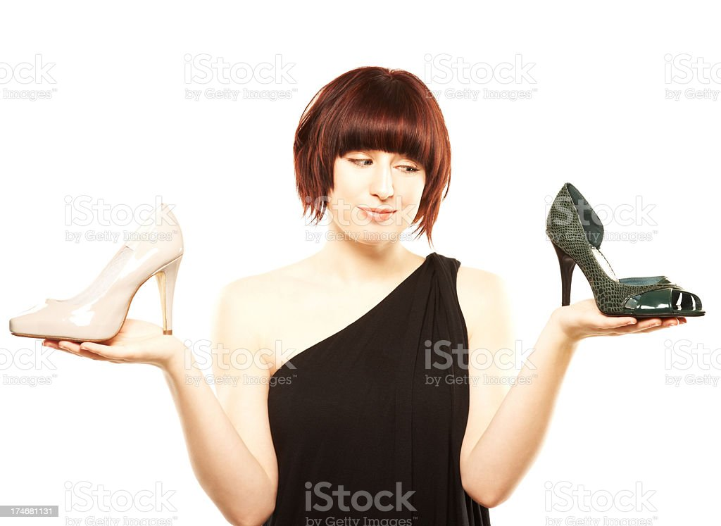 Young woman trying to choose between two pairs of shoes royalty-free stock photo