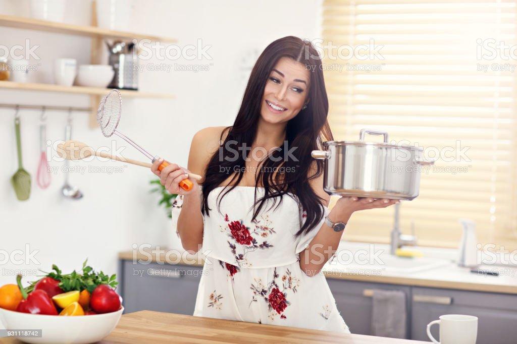 Genç kadın mutfakta bir şeyler pişirmek için çalışıyor - Royalty-free Beyaz Tenli Stok görsel