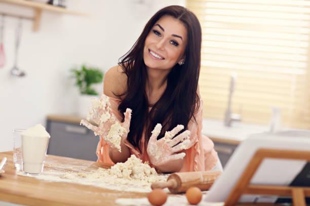 junge frau, die versucht zu pierogi in küche - pfannen test stock-fotos und bilder