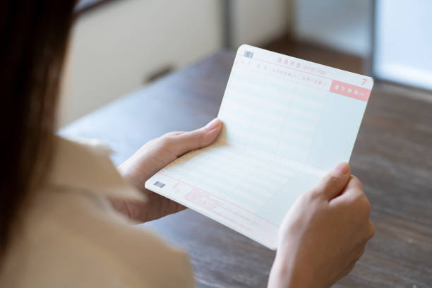 机の上で通帳を開こうとする若い女性 ストックフォト