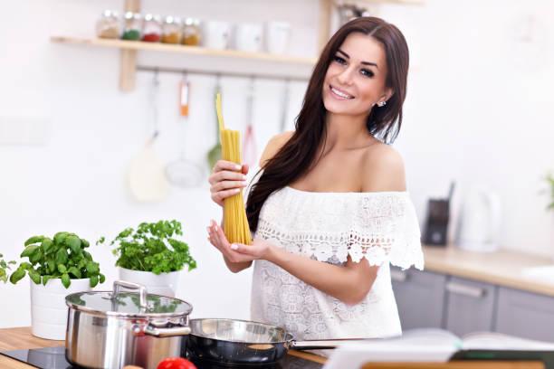 junge frau versucht, nudeln in küche vorzubereiten - pfannen test stock-fotos und bilder