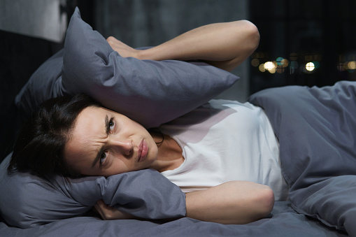 Young Woman Trying To Sleep But Disturbed By Noisy Neighbors And Covering Ears With Pillows Stock Photo - Download Image Now