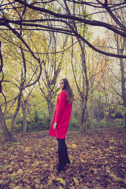 Young woman turning around in the forest, wearing a long, red jacket. stock photo