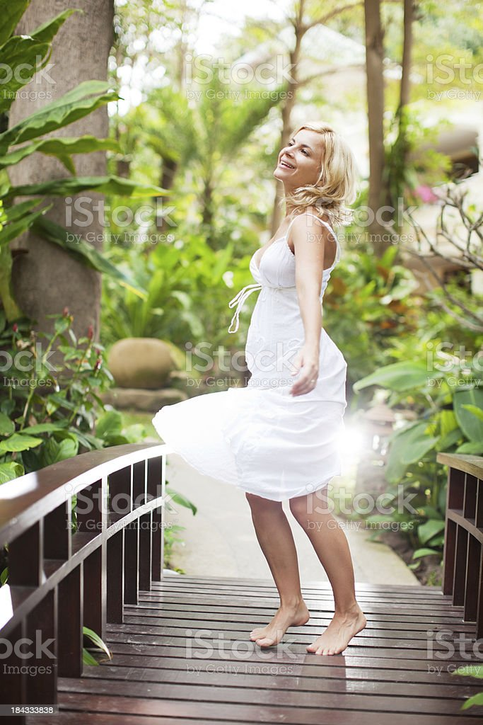 Young woman turns on the wooden bridge. royalty-free stock photo