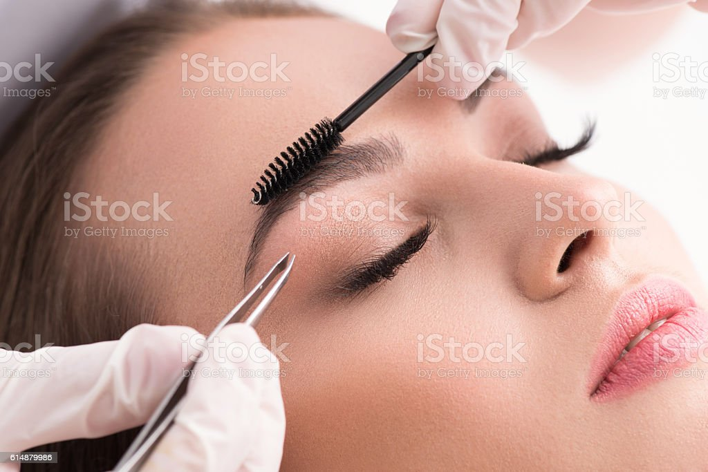 Young woman tweezing her eyebrows in beauty saloon – Foto