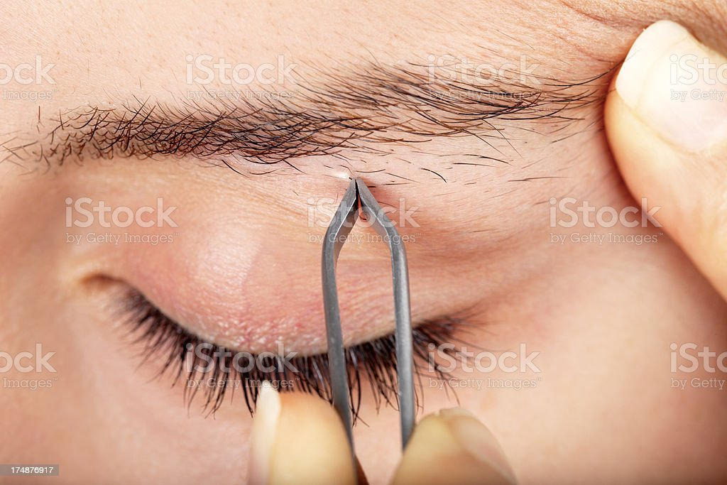 Young Woman Tweezing Her Eyebrows - Royalty-free 20-29 Years Stock Photo
