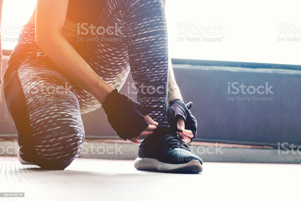 Young woman tying her shoelaces before exercise in gym