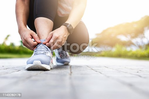Young woman tying jogging shoes.