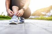 Young woman tying jogging shoes.