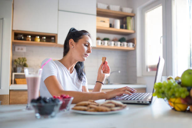 Young woman typing an e-mail on laptop at home stock photo