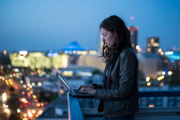 young woman typing in her laptop, illuminated cityscape of Berlin in background, twilight stock photo