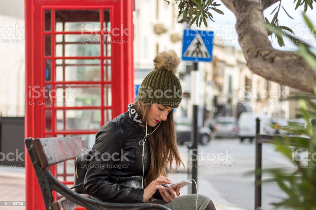 Young woman typing message outside stock photo
