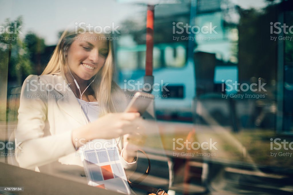 Young Woman Typing On Her Smart Phone In Public Transportation. stock photo