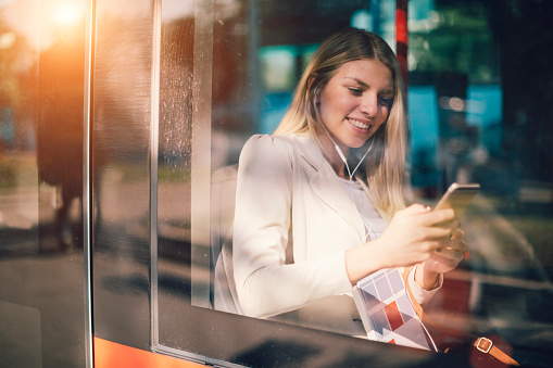 Young Woman Texting On Her Smart Phone In Public Transportation. She is sitting, holding books and typing on her smart phone. Unrecognisable people in background. Shot from outside. Reflections on bus window.