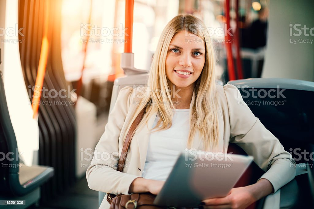 Young Woman Typing On Her Tablet In Public Transportation. stock photo