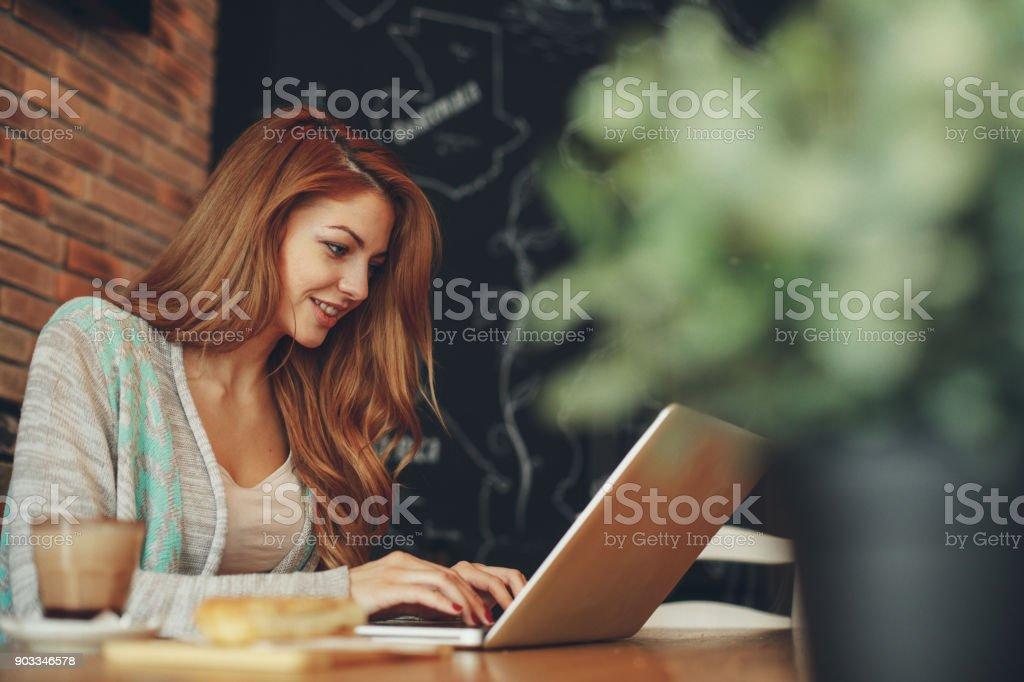 Junge Frau, die Eingabe auf Laptop im café – Foto