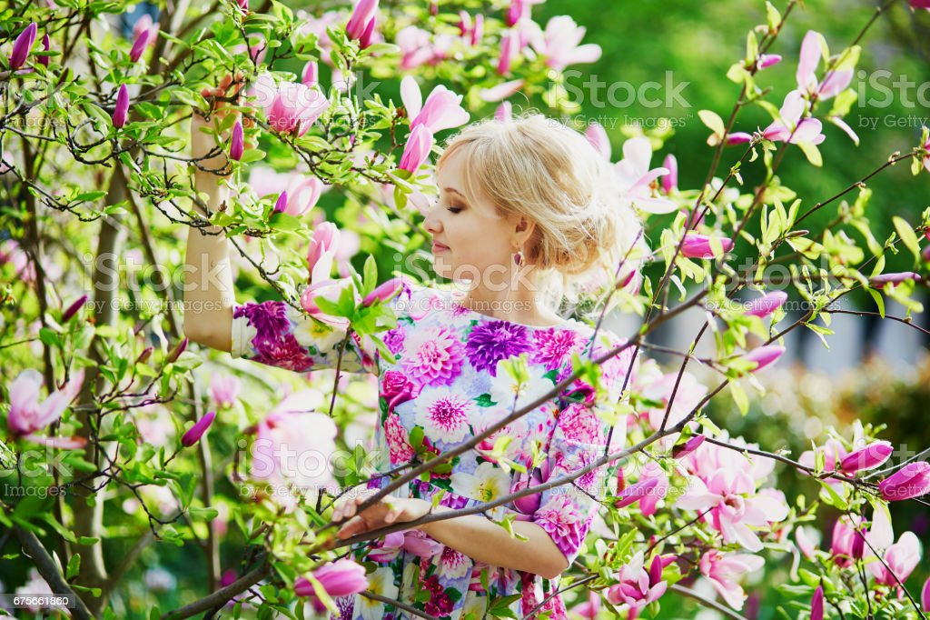 Young woman under blooming magnolia tree on a spring day royalty-free stock photo