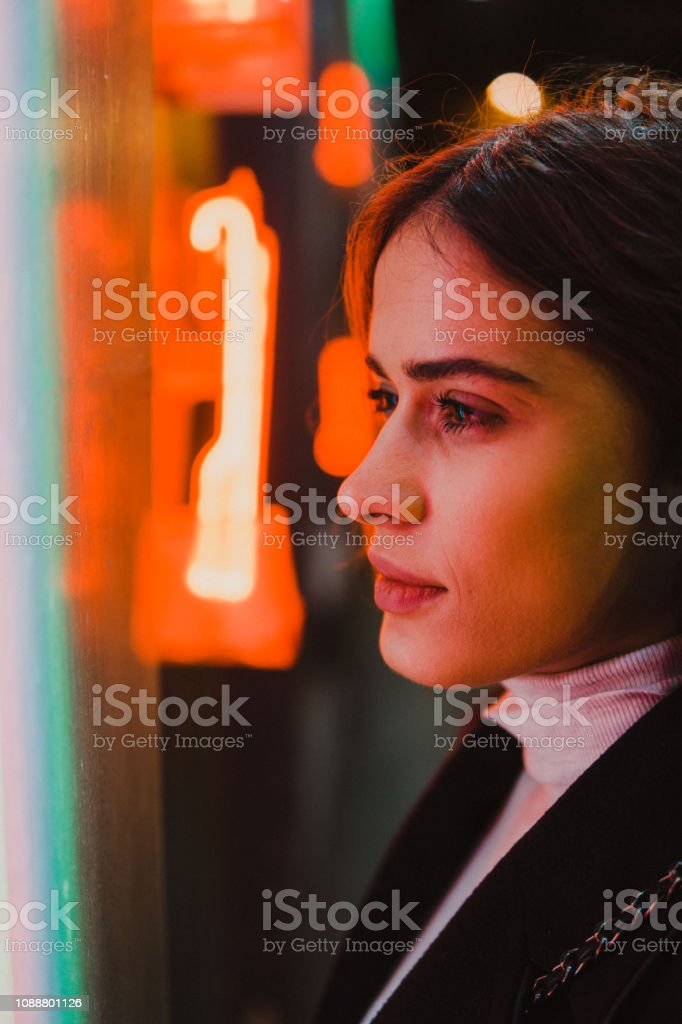 Young woman under the colorful neon lights. stock photo