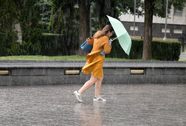 Young woman under umbrella during sudden spring shower