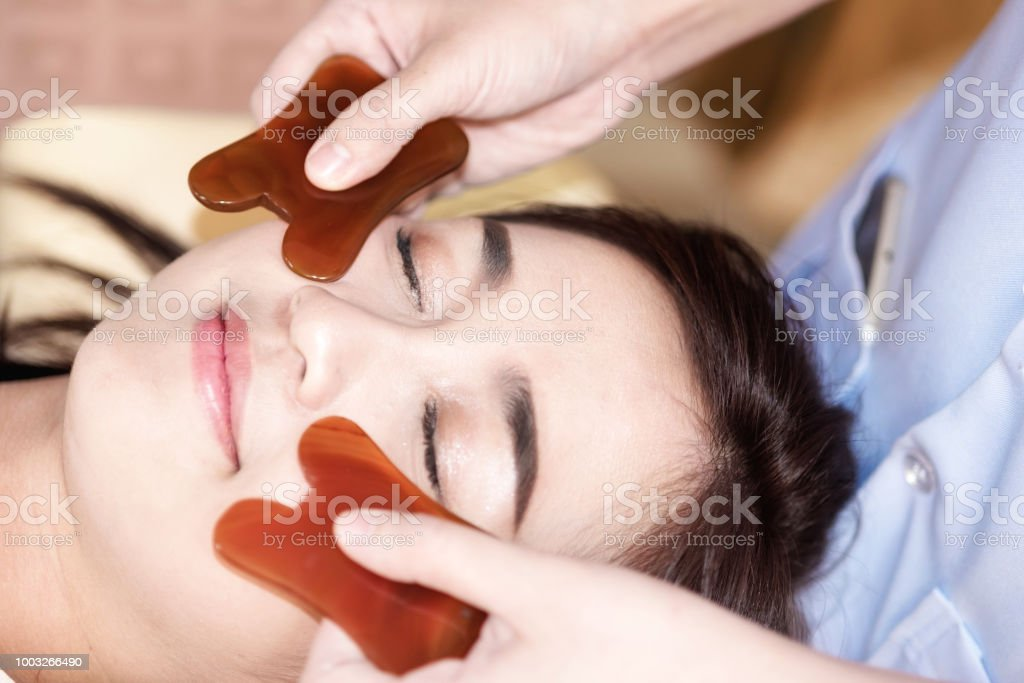 young woman undergoing acupuncture treatment by jade at the health...