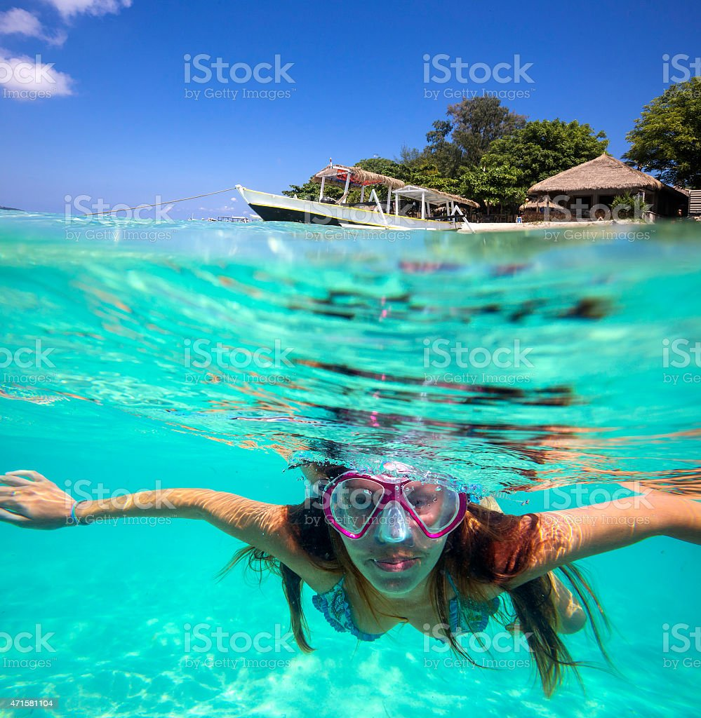 A young woman underwater swimming stock photo