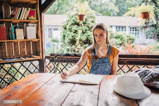 One woman, beautiful young woman  sitting in backyard , learning for exam.
