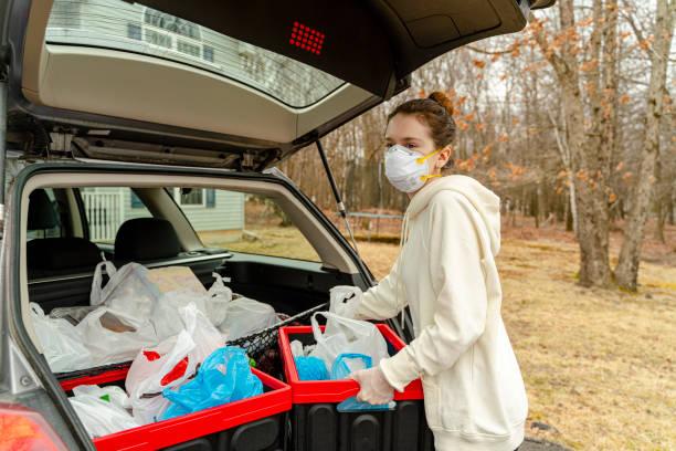Junge Frau entladen Kunststoff wiederverwendbare Behälter gefüllt mit Lebensmitteln aus dem Kofferraum des Autos geliefert werden. – Foto
