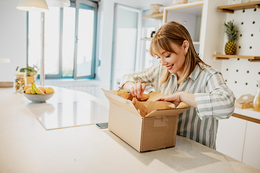 A young woman is at home, she unpacks delivered package