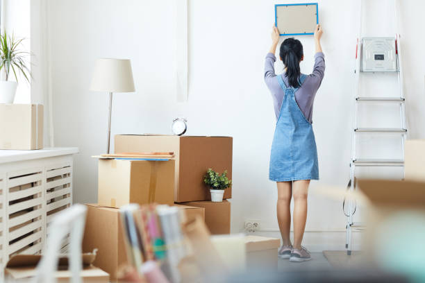 Young Woman Unpacking Boxes in New Home stock photo