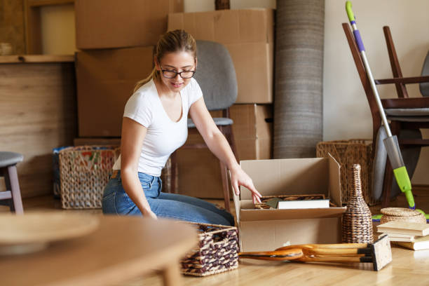 Young woman unpacking cardboard boxes at new home. stock photo