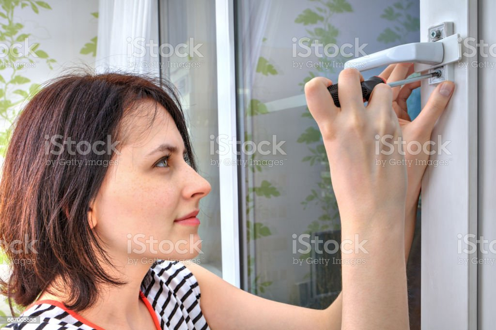 Young woman unscrews a window handle using screwdriver. stock photo