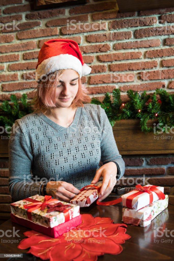 Photo libre de droit de Jeune Femme Déballer Un Cadeau De Noël