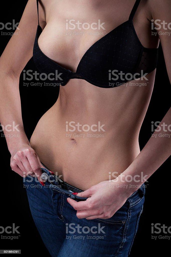 Young woman unzips pants stock photo