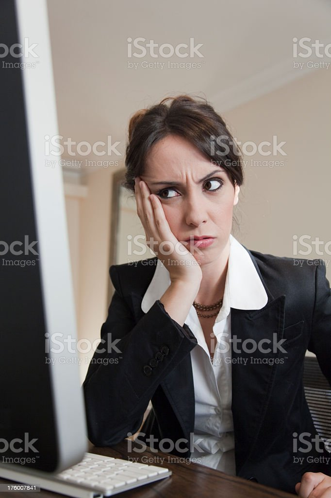 Young woman upset in front of computer display royalty-free stock photo