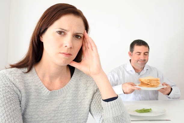 young woman upset when her partner eat and enjoys carbohydrates - metabolic syndrome stock photos and pictures