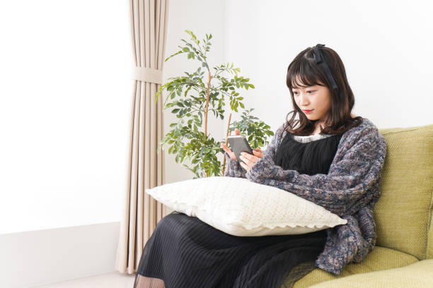 若い女性は自宅でスマートフォンを使用しています ストックフォト