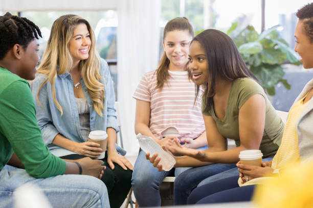 Young woman uses humor when sharing with support group A young woman sits in a circle with her counseling support group.  She holds a water bottle as she leans forward and shares a humorous story. group therapy stock pictures, royalty-free photos & images