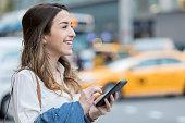 若い女性がスマート フォンを使用して新しい都市を移動するには
