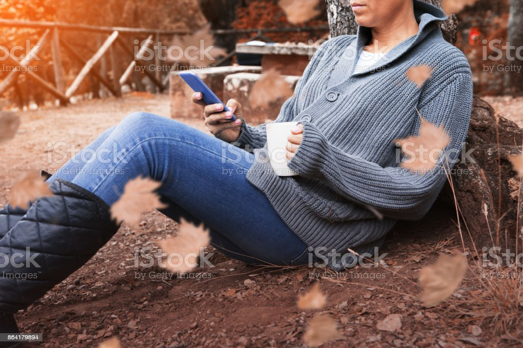 Young woman uses smartphone in autumn park royalty-free stock photo