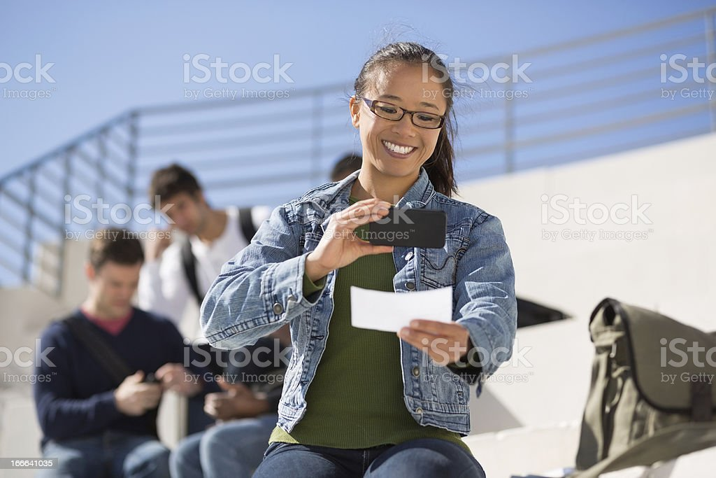 Young woman uses smartphone to deposit a check stock photo