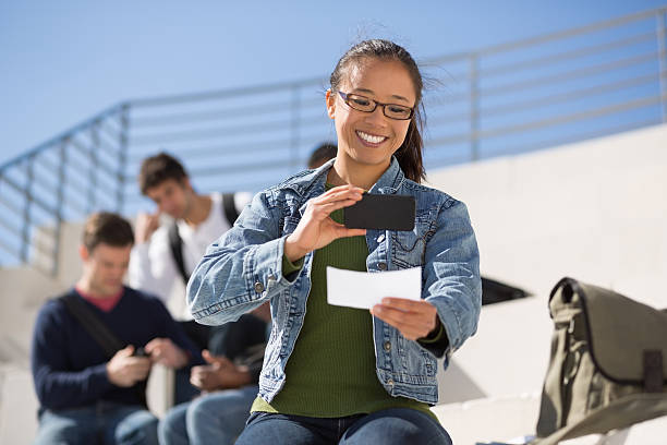 young woman uses smartphone to deposit a check - bank deposit slip stock pictures, royalty-free photos & images
