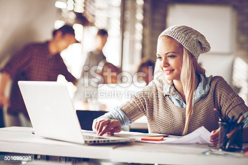 istock Young woman usign laptop in office 501099098