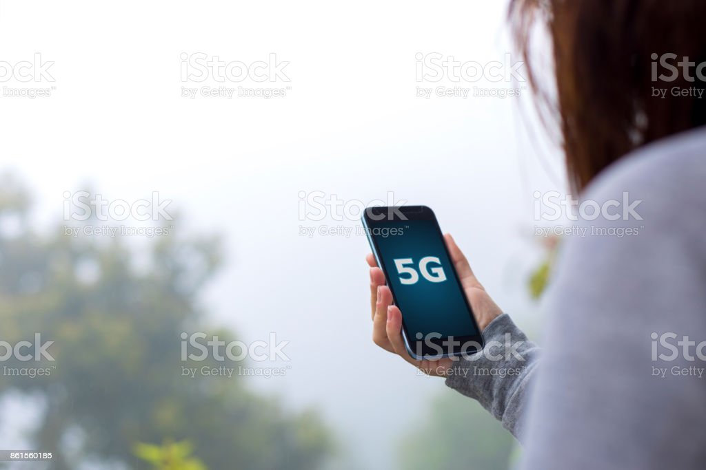 Young woman using 5G on smartphone stock photo